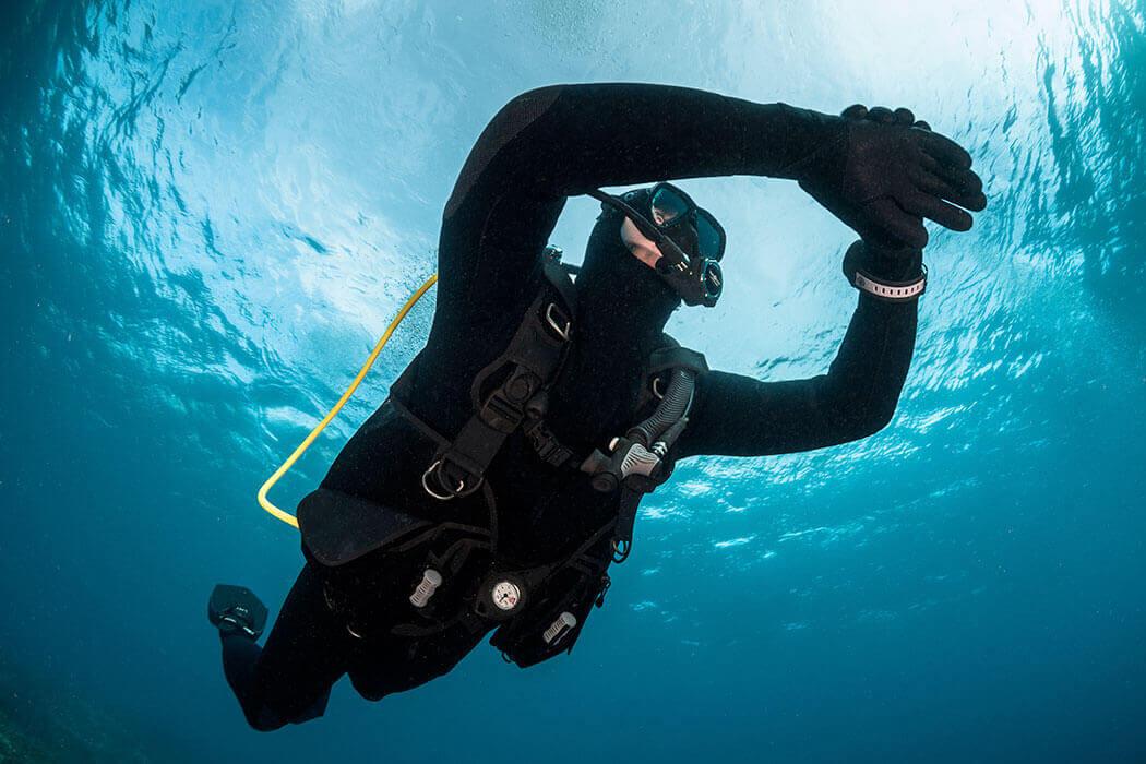 Un plongeur regarde sa montre de plongée dans la baie de Cavalaire